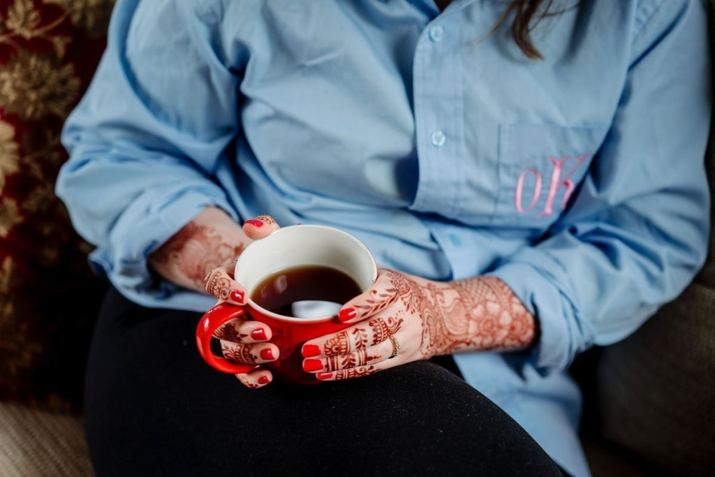 bride holds a coffee mug while her hands are covered in hennah from mehndi party