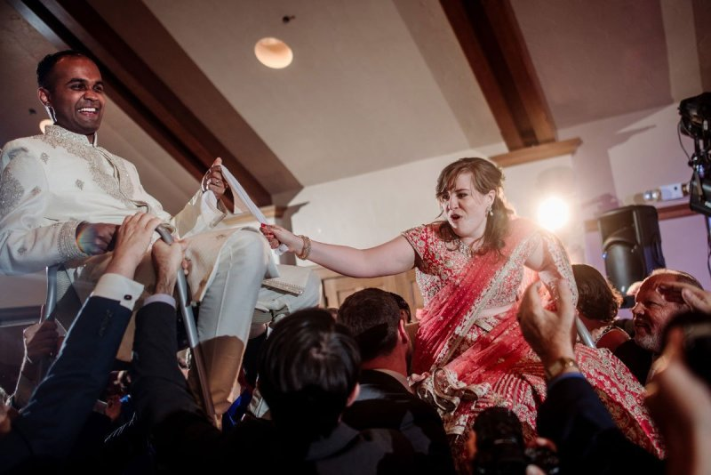 bride and groom are hoisted in chairs as part of the hora dance