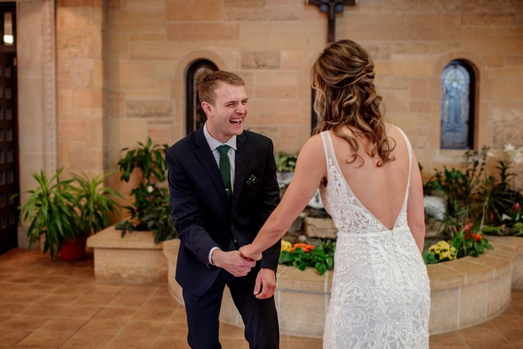 groom laughs with joy while he sees bride for first time