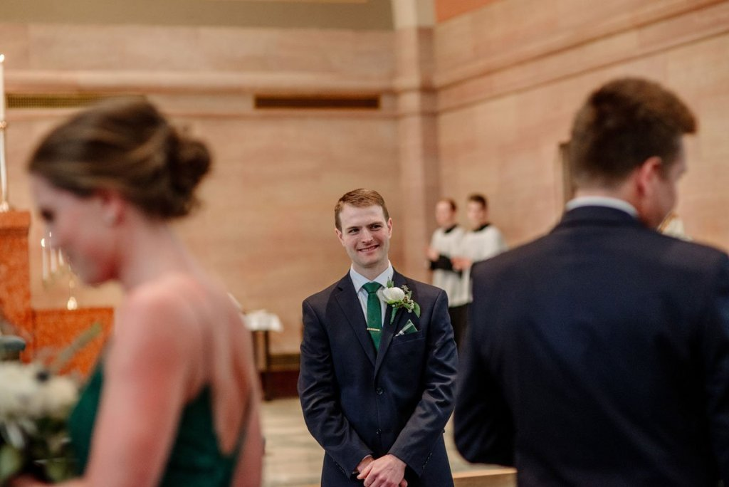 groom waits for bride at top of aisle