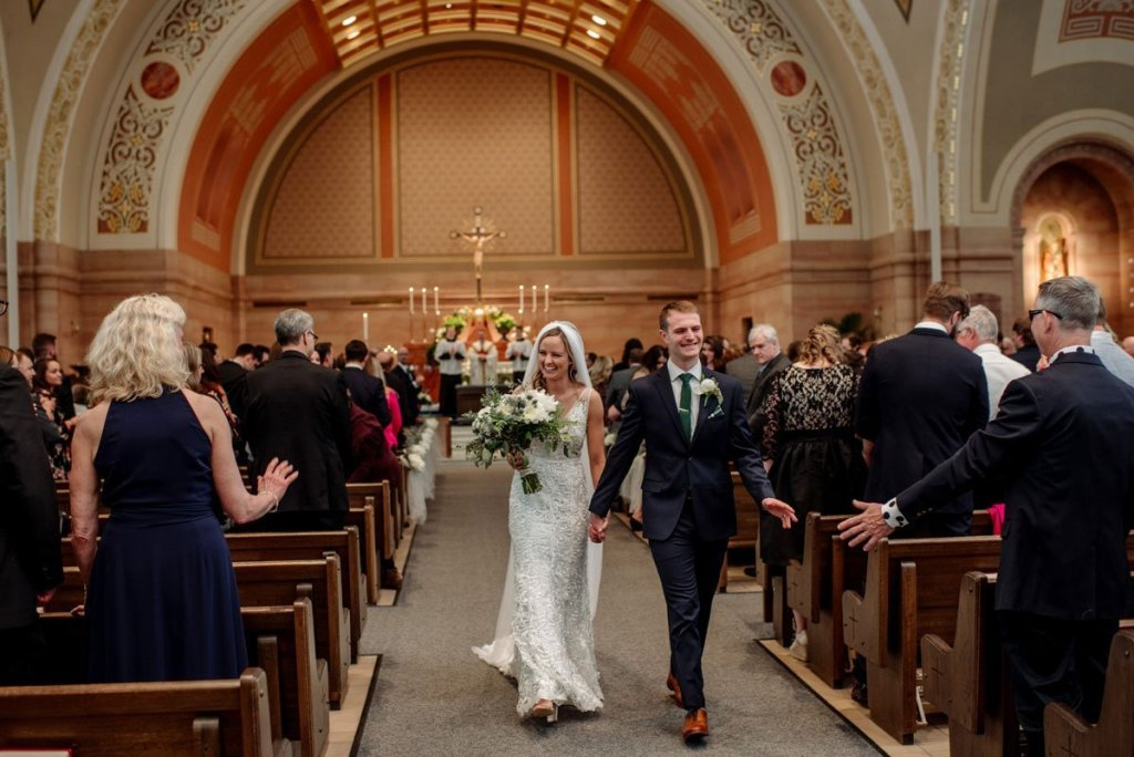 bride and groom walk down aisle after first kiss as man and wife