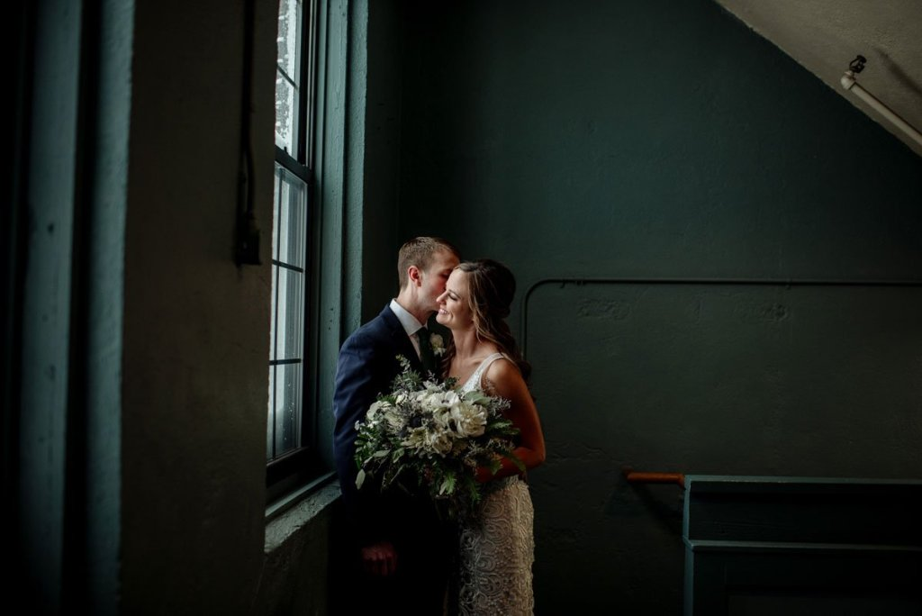 couple stands by window and groom kisses brides cheek