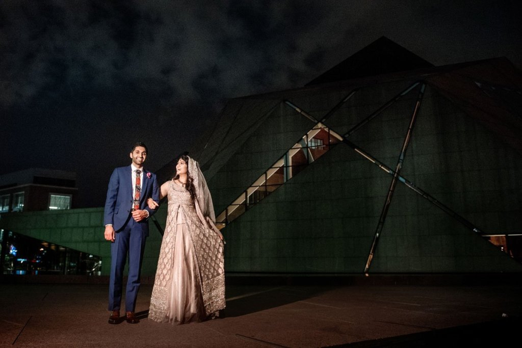 couple outside McNamara center at night with building behind them. Bride is wearing a pink sari and groom has a navy suit