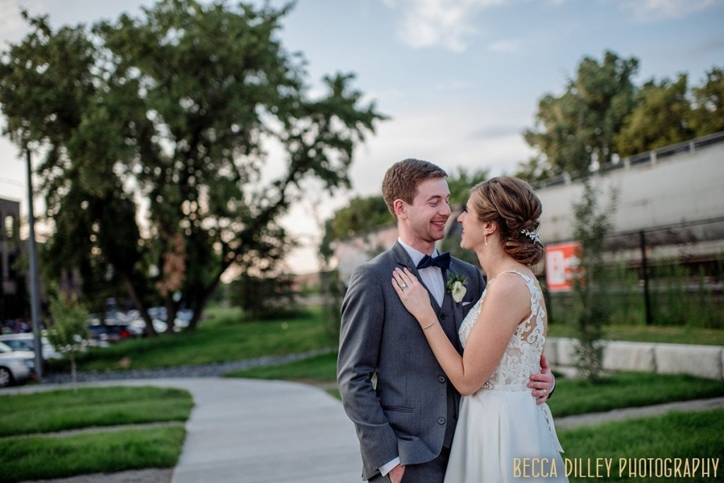 bride and groom outside solar arts building in ne minneapolis with train behind them