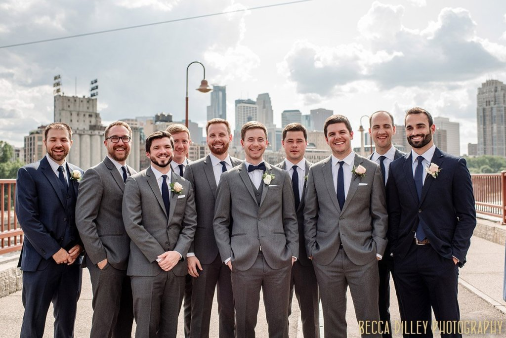 Groom with 9 groomsmen laughing on stone arch bridge in minneapolis