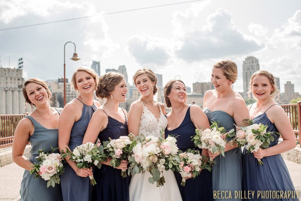 Bride with 6 bridesmaids all laughing together on stone arch bridge in Minneapolis