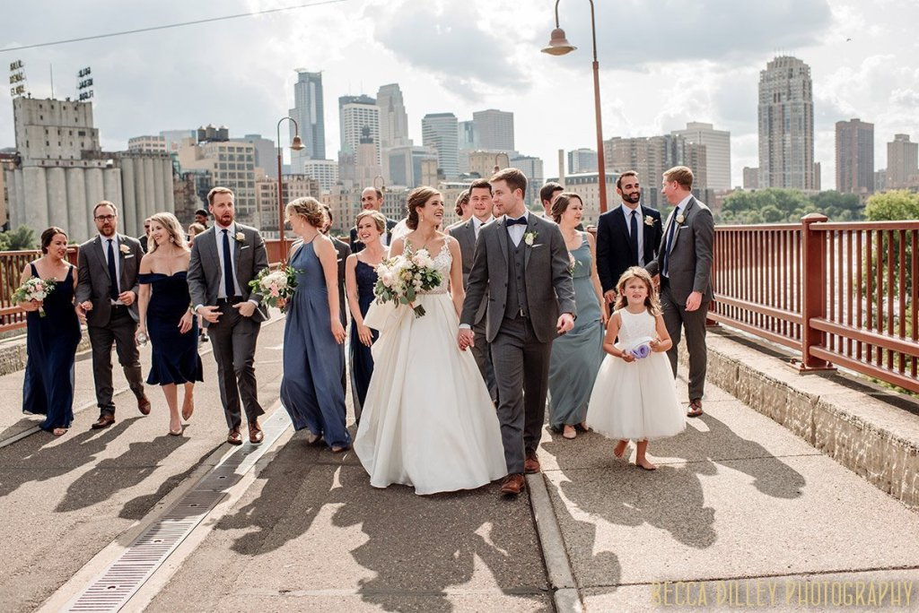 large wedding party in shades of blue walks down stone arch bridge in minneapolis