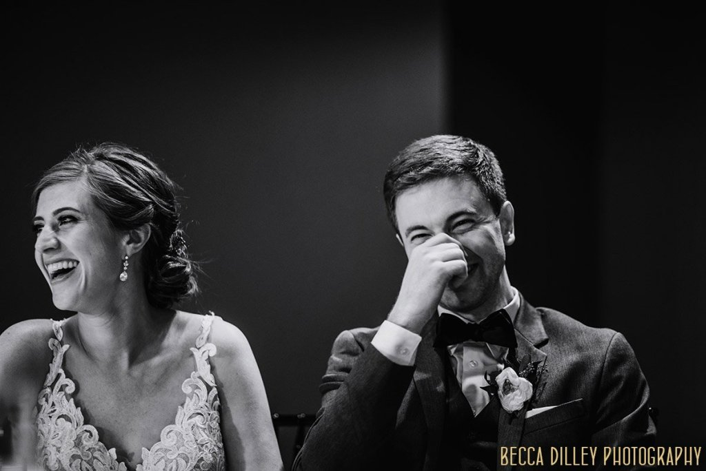 groom laughs during a speech at  solar arts wedding reception