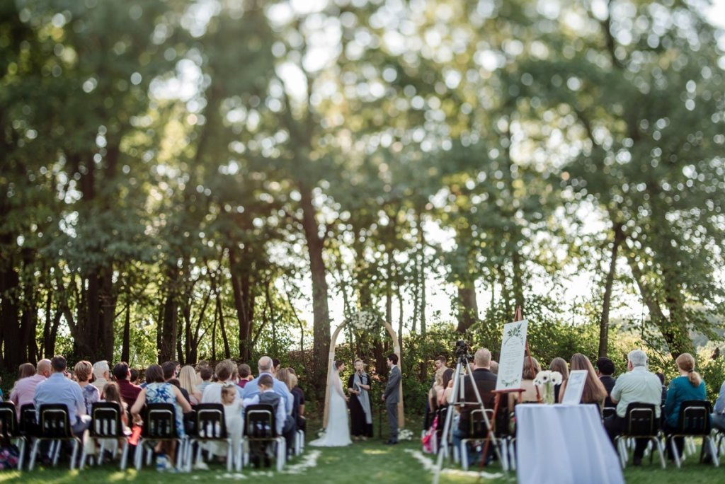 tilt shift lens used on outdoor ceremony so that trees are blurry but couple is in focus voyageur wedding environmental center mn