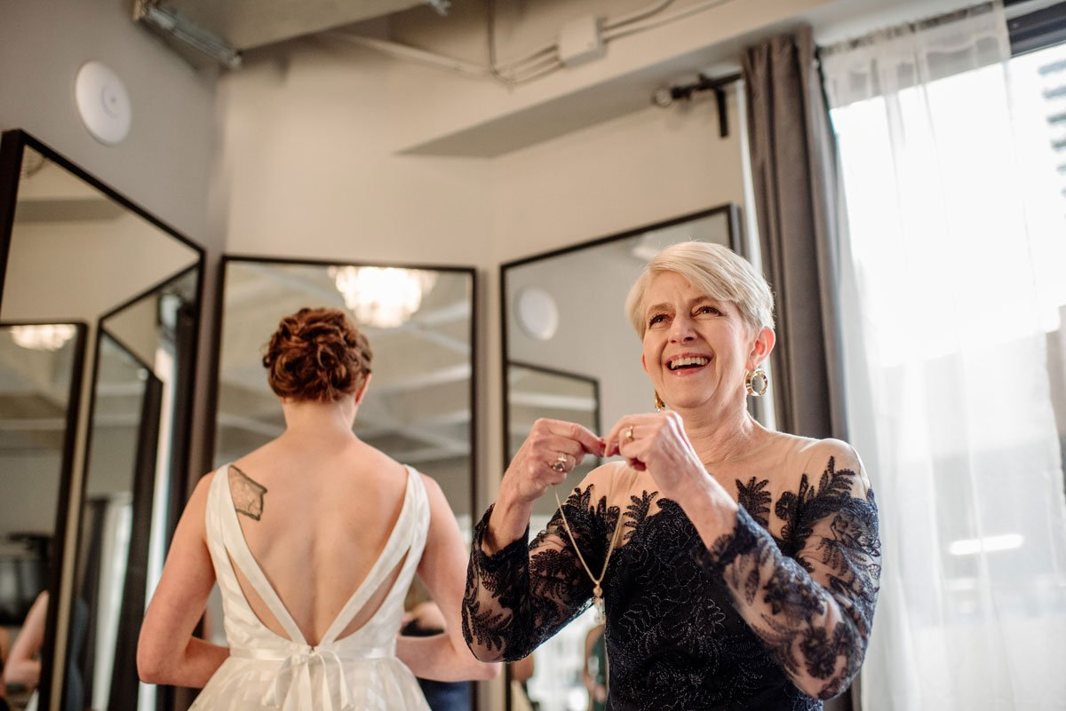 mother of the bride laughs as she puts necklace on bride before lumber exchange wedding minneapolis