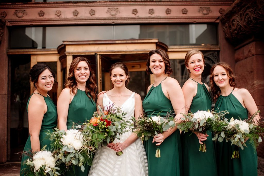 bride and 5 bridesmaids with emerald green dresses outside of the lumber exchange