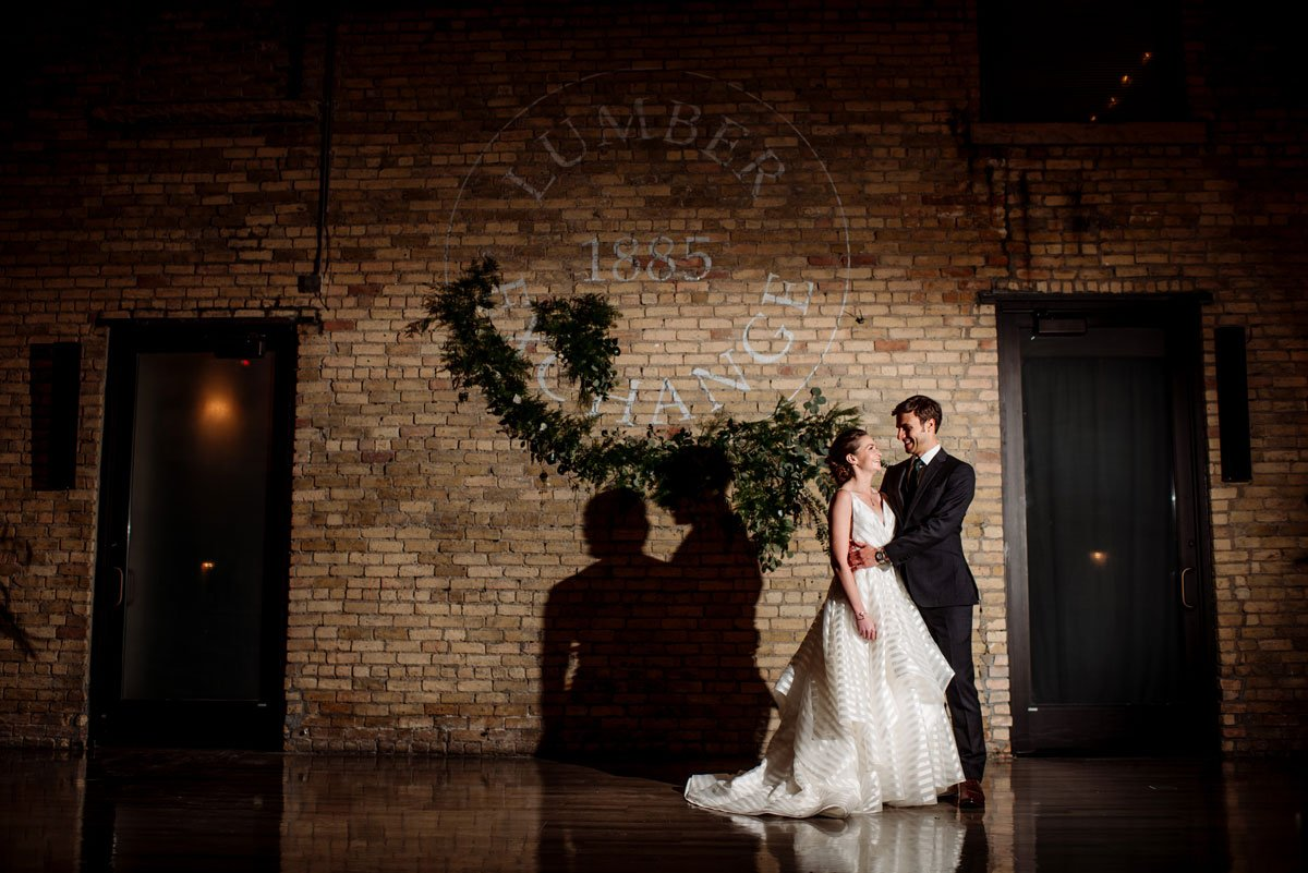 bride and groom in front of brick wall with dramatic lighting at lumber exchange
