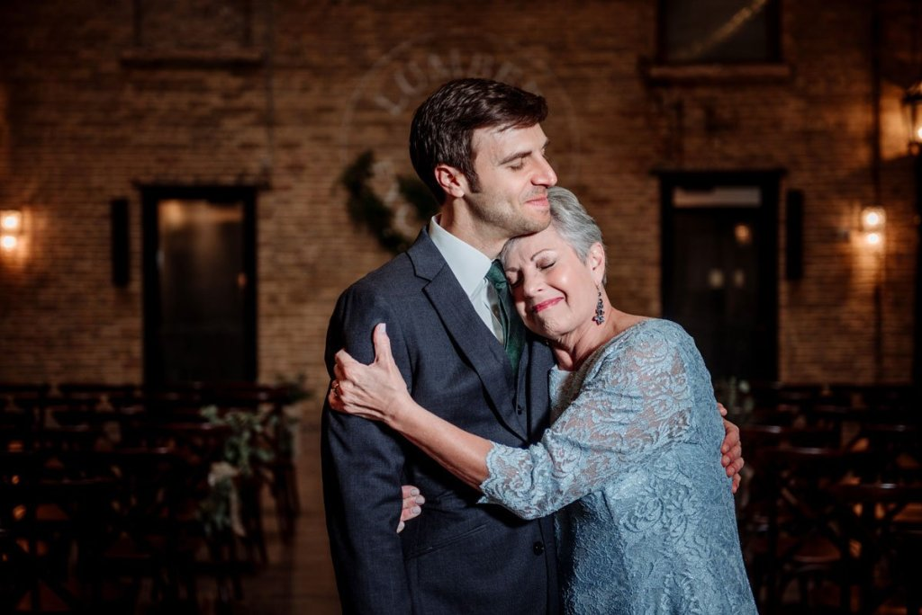 groom and mother share a moment during formal portraits by hugging