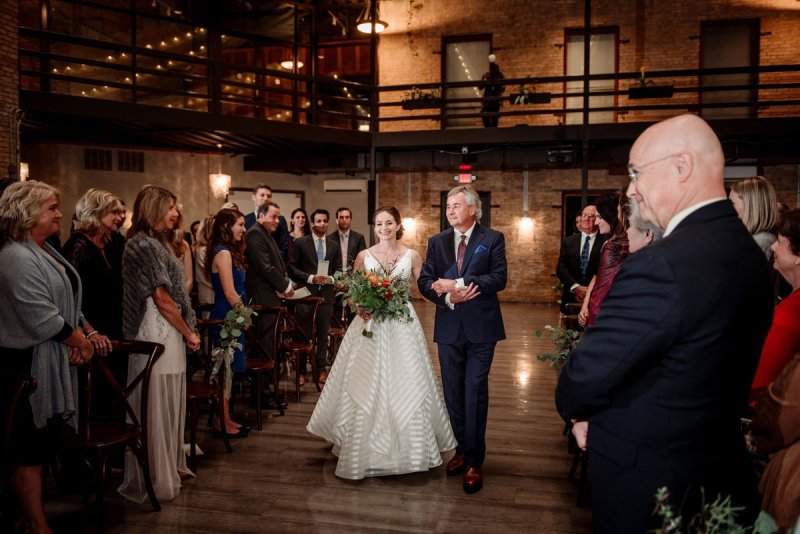 bride and father walk down aisle at lumber exchange minneapolis