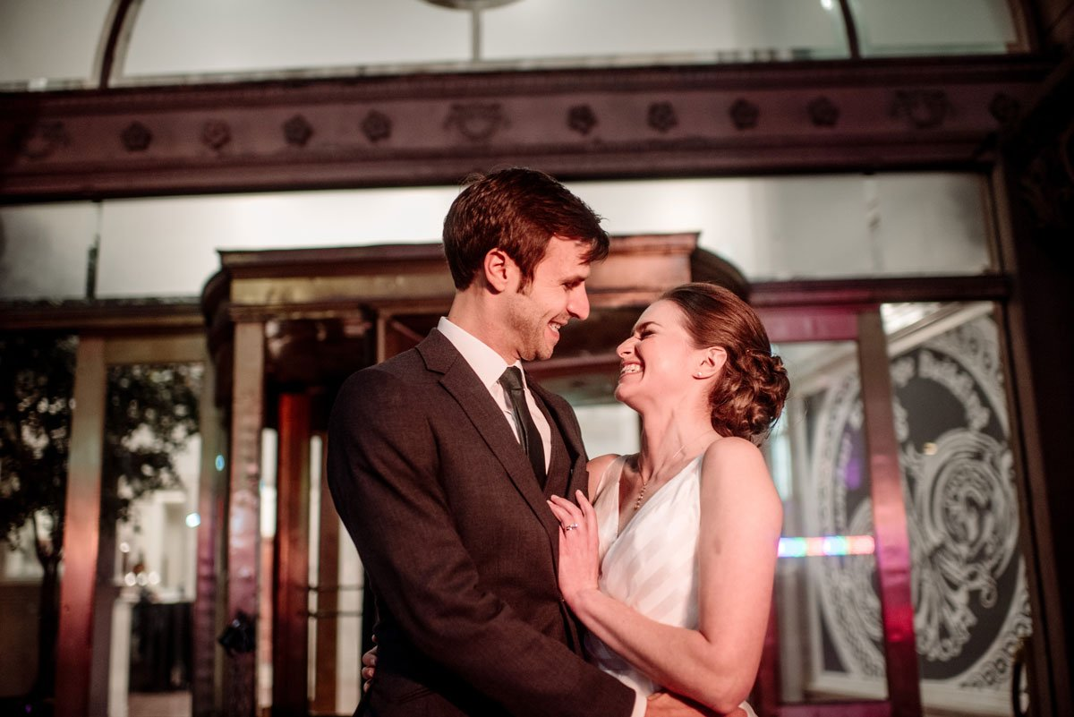 bride and groom laugh in each others arms outside the lumber exchange minneapolis