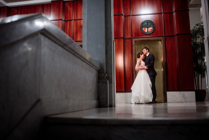 bride and groom embrace by elevators of lumber exchange building