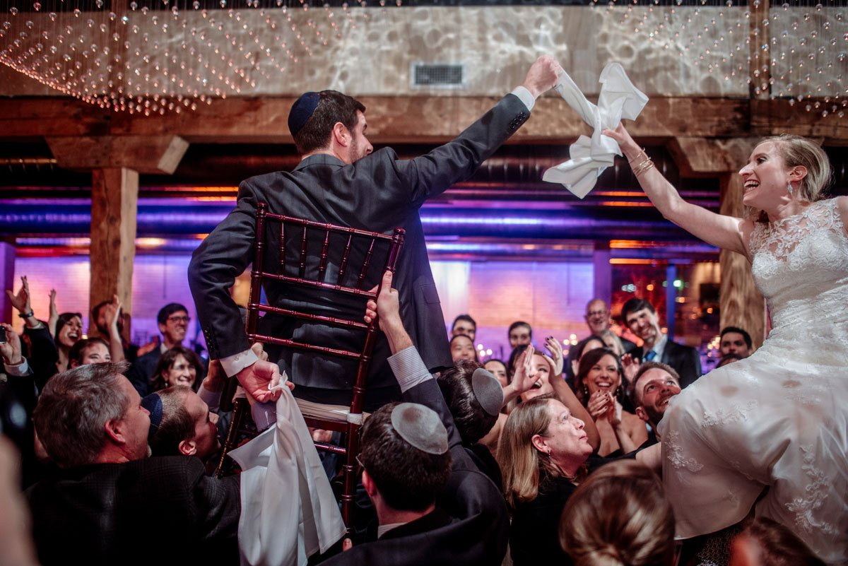 Dancing the hora, the bride and groom are up in chairs new years eve wedding Minneapolis event center
