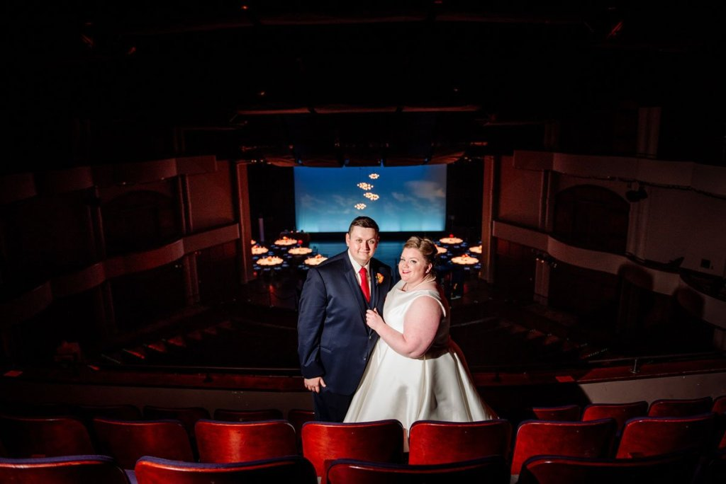 bride and groom with dramatic lighting inside performance space of washington pavilion wedding sioux falls