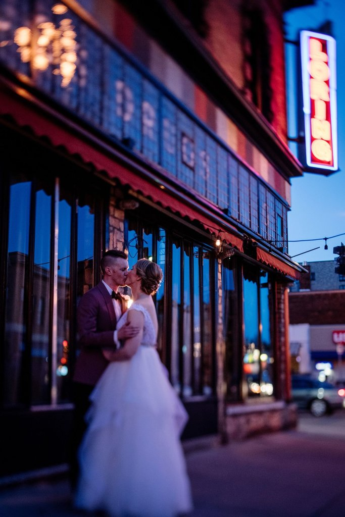 tilt shift image of couple outside loring restaurant at night in dinkytown minneapolis after their wedding