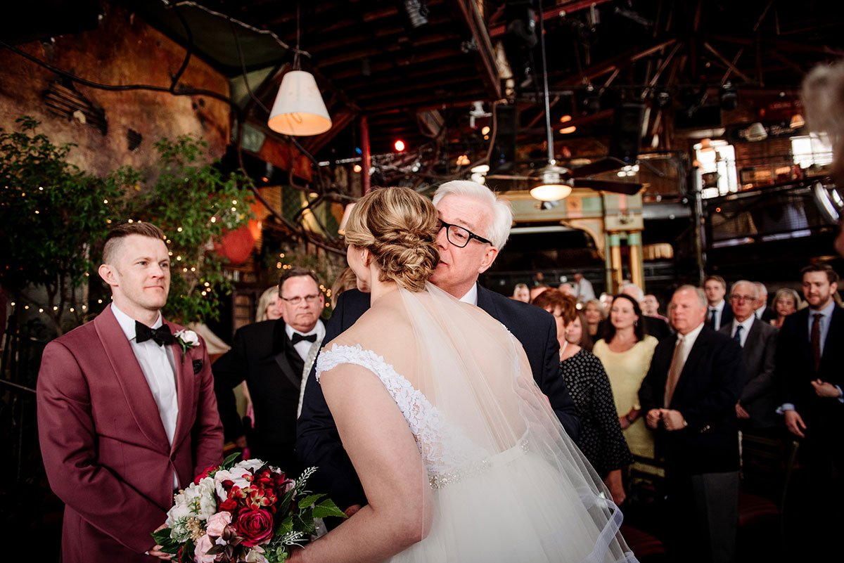 bride and father exchange bugs at end of aisle before loring restaurant wedding minneapolis