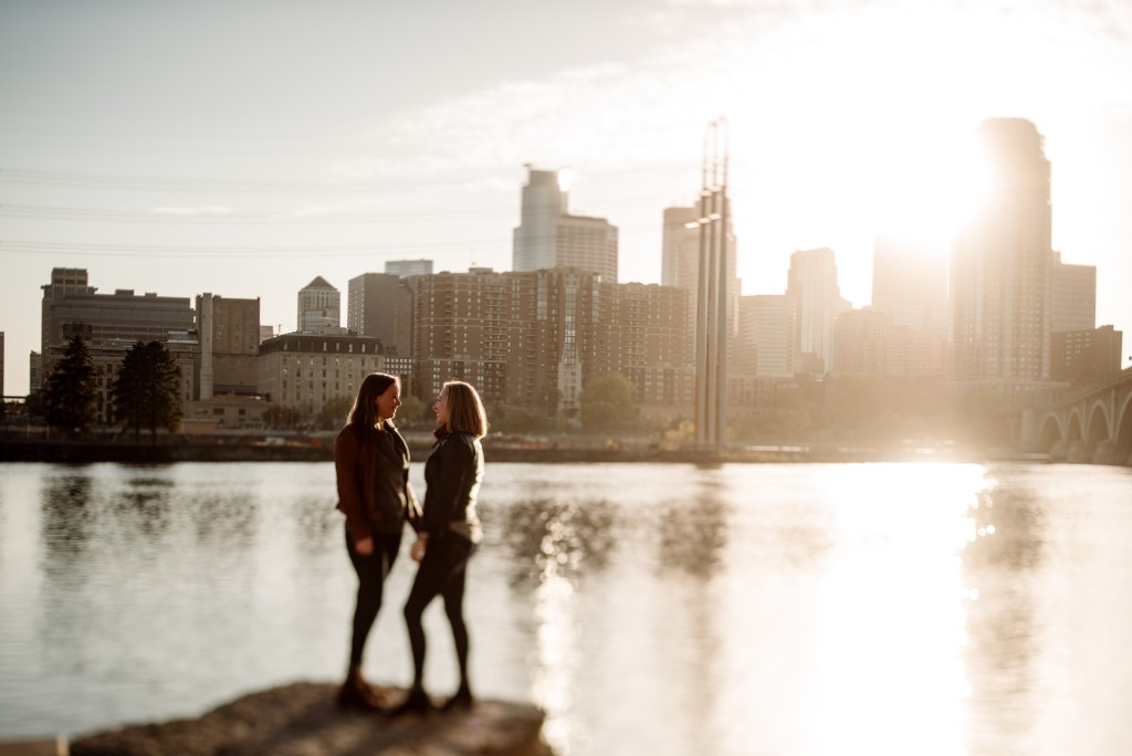 couple in silhouette with Minneapolis skyline behind them at golden hour  - St Anthony main engagement photos