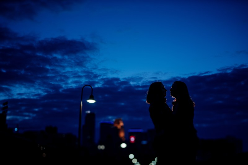 silhouettes of two women embrace with with blue night sky and minneapolis skyline