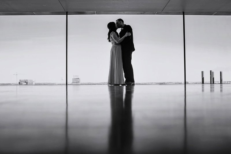 couple kiss in black and white portrait with windows behind them