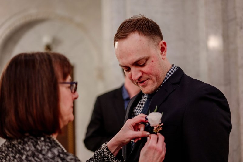 mother of the groom pins on boutonniere at city hall wedding minneapolis