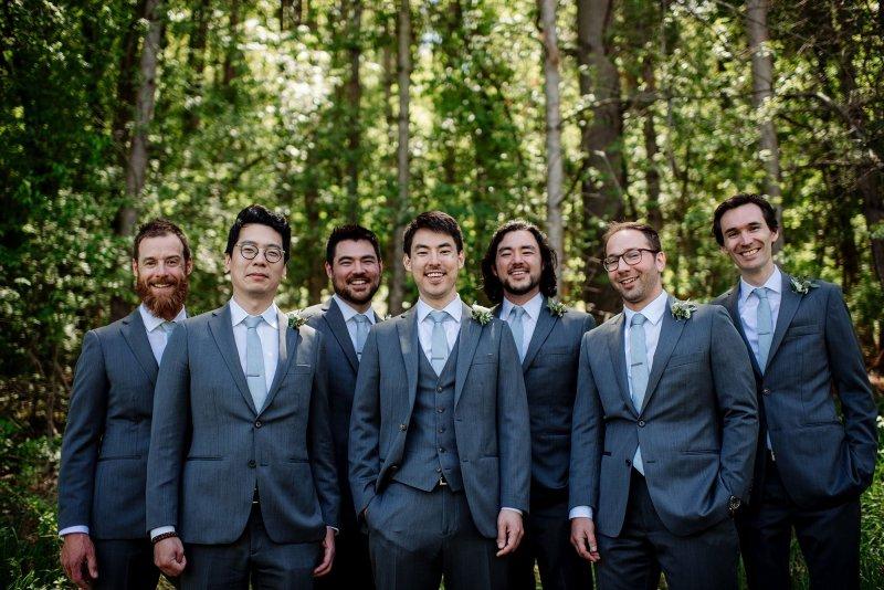 groomsmen in woods at wedding at round barn