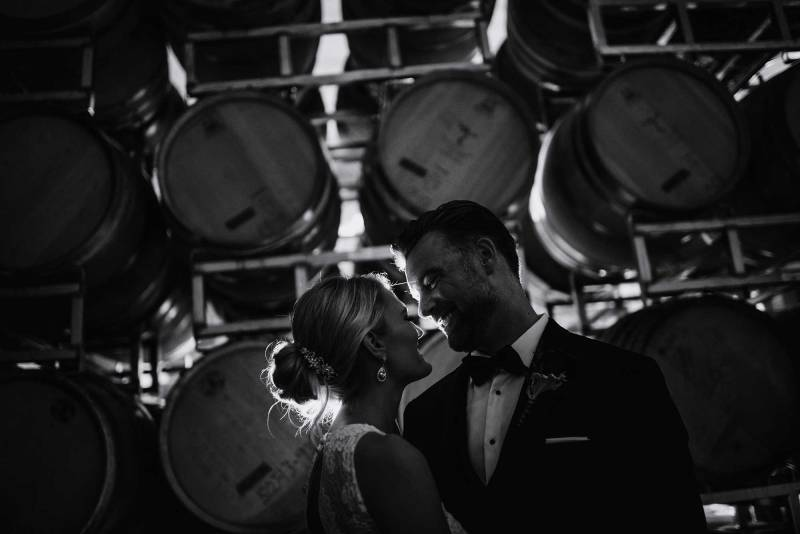 bride and groom with casks of wine 7 vines vinyard wedding mn