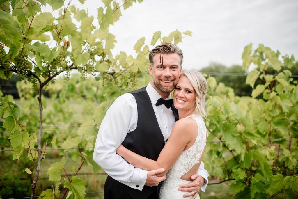 bride and groom in vines at 7 vines vinyard wedding mn