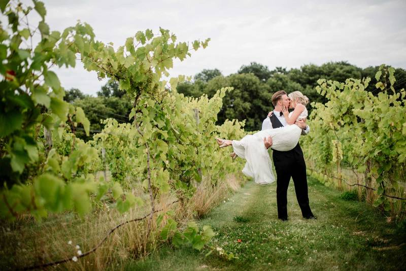 groom holds bride in the vinyard of Delano