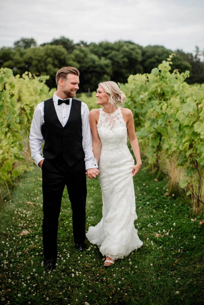 bride and groom laughing while walking between vines at seven vines vinyard