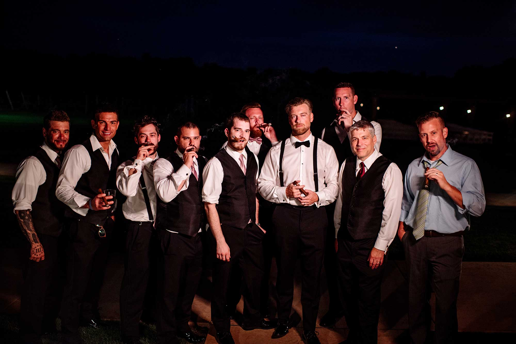 groom and groomsmen enjoy a cigar on the patio at end of 7 vines vinyard wedding mn