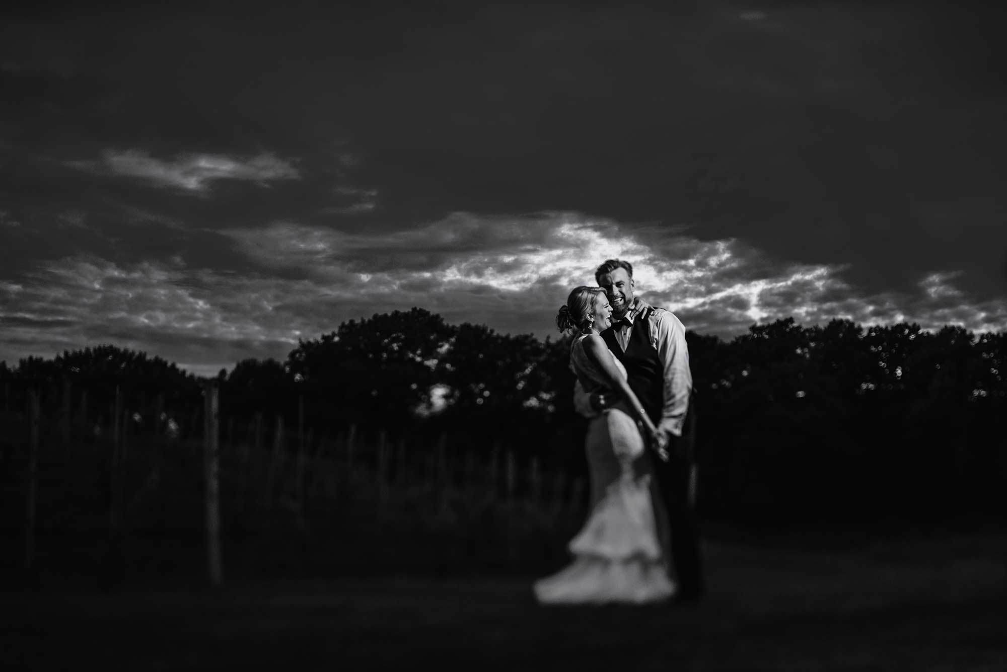 black and white photo of couple with dramatic clouds at 7 vines vinyard wedding mn