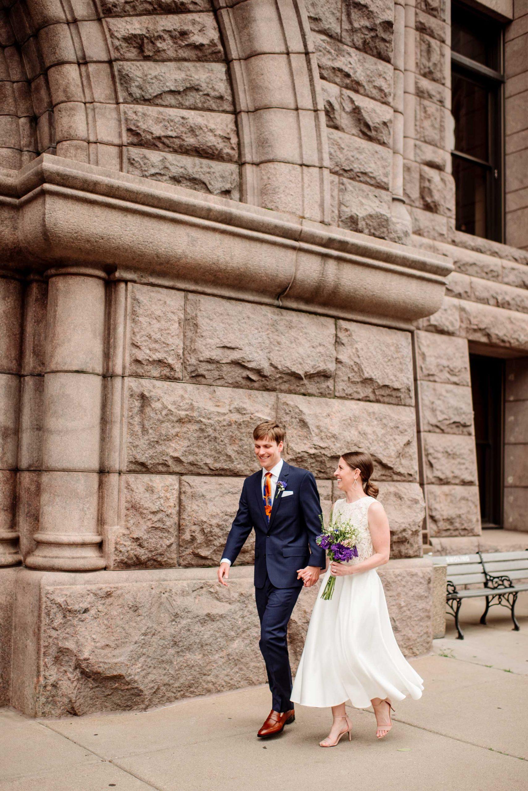 couple walks outside Minneapolis city hall wedding
