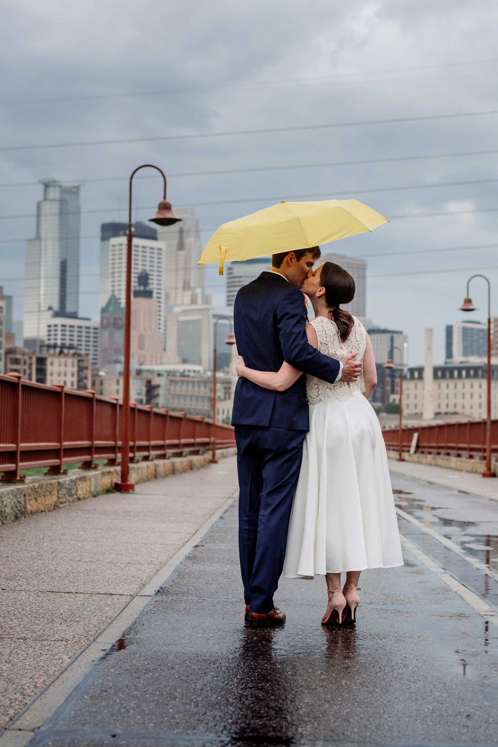 couple walking with yellow umbrella minneapolis