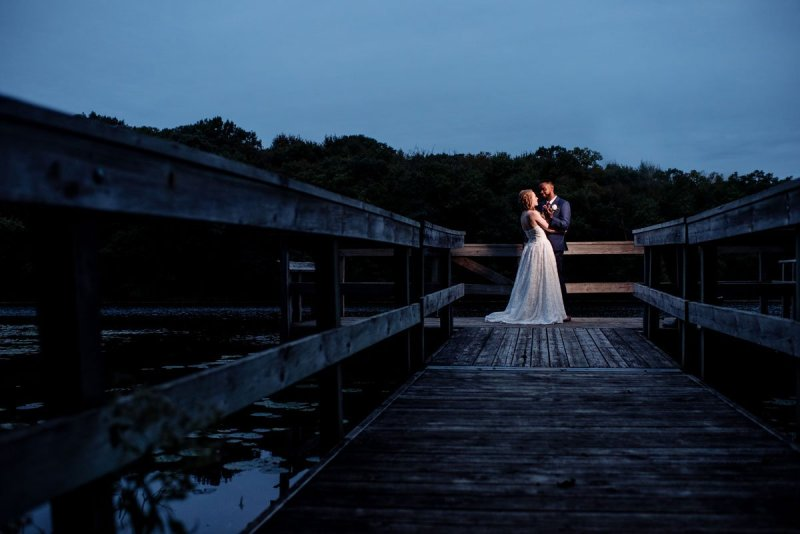 couple on dock at night with blue skies mn camp wedding
