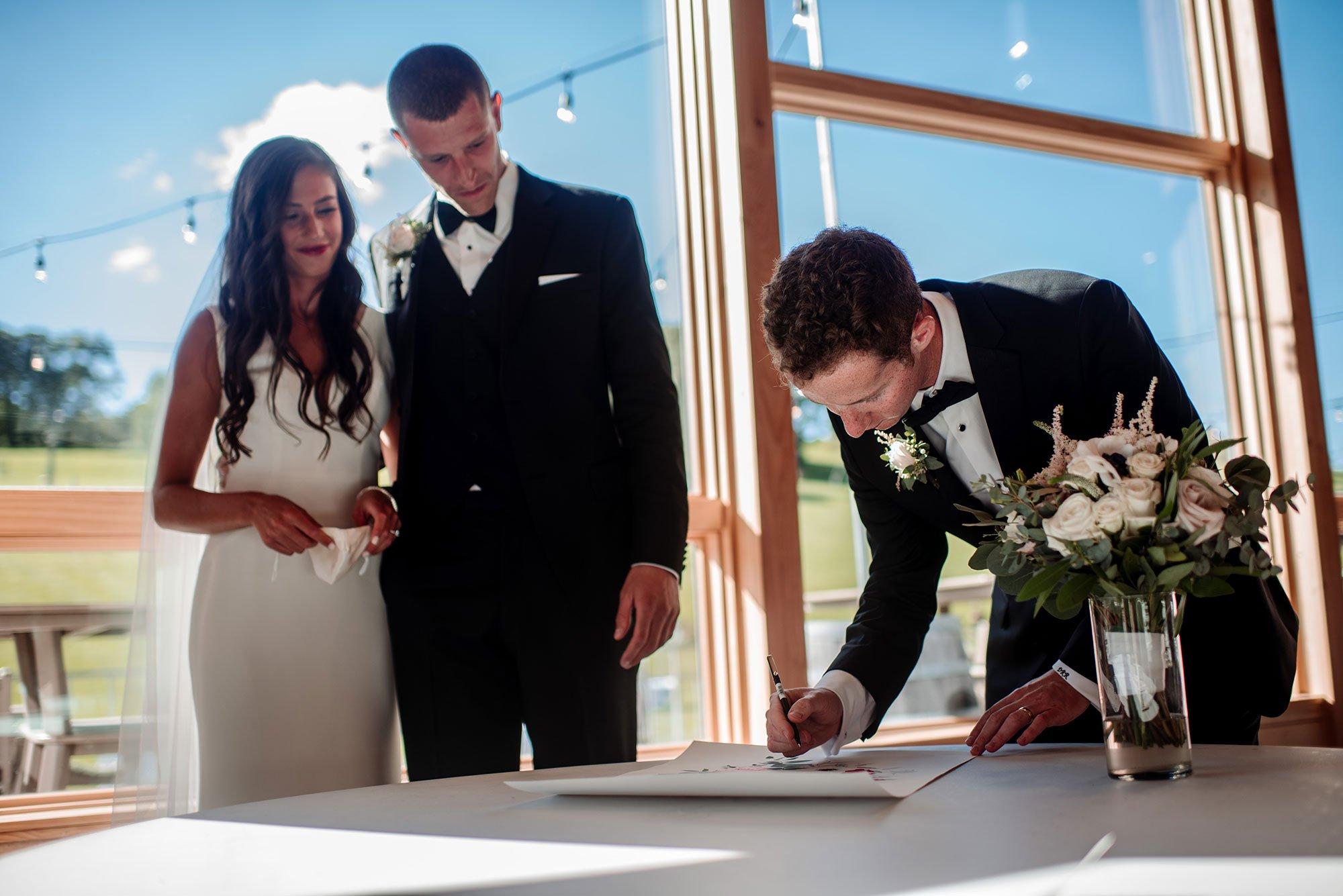 bride and groom sign the ketubah at hyland hills mn wedding