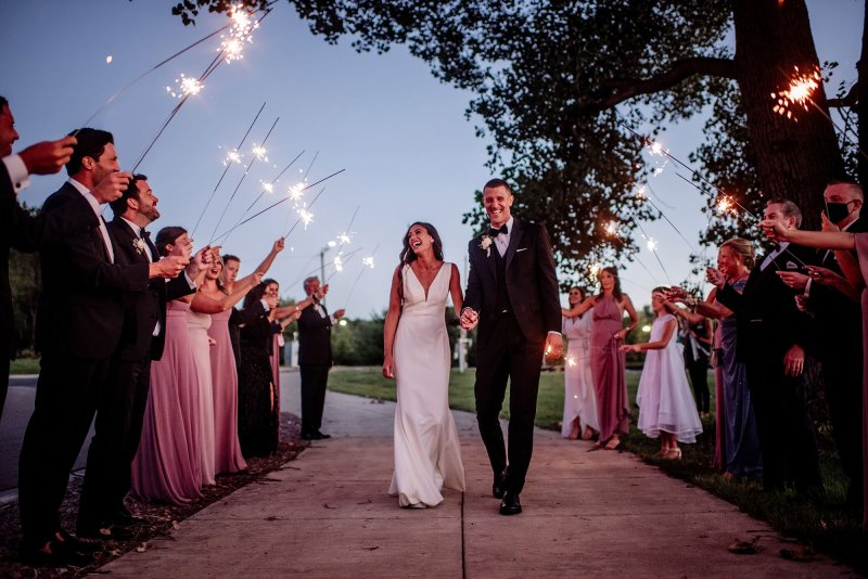 bride and groom celebrate with sparklers at the end of their wedding at hyland hills mn