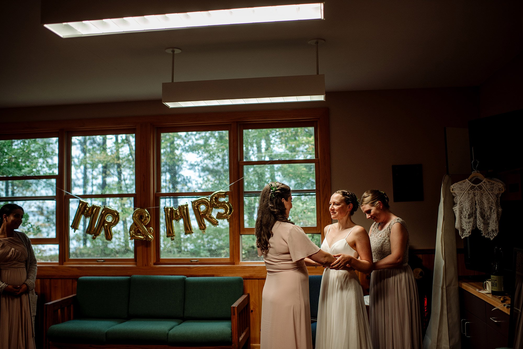 bride getting ready in lodge MN wedding at Camp Miller