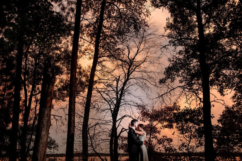 brideg and groom with silhouette trees at Sunset MN wedding at Camp Miller