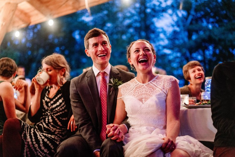 couple laughing during toasts at lodge MN wedding at Camp Miller
