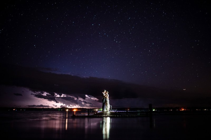 couple on dock at starry night MN wedding at Camp Miller