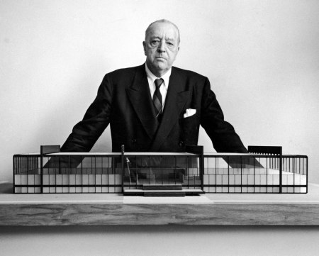 A photograph of Mies van der Rohe with a model of Crown Hall at the Illinois Institute of Technology.