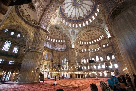 """Ottoman architect Sedefkâr Mehmed Ağa designed the Sultan Ahmed Mosque for Ottoman Sultan Ahmed in the early 17th Century. The interior is dominated by the multiple domes above, colored light from the stained glass windows and many thousands of mosaic tiles adorning the walls. The predominance of blue tiles has given the Istanbul shrine its popular name, """"the Blue Mosque."""""""
