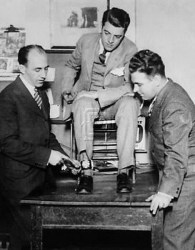 A photograph of Tom Howard (center) with the ankle camera he used to photograph Ruth Snyder's execution.