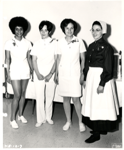 "Children's Hospital nurses were not required to wear uniforms until 1885. This photograph from 1971 shows four nurses modeling uniforms for a ""nurses through the years"" fashion show, including an imagined uniform of the future featuring hot pants!"