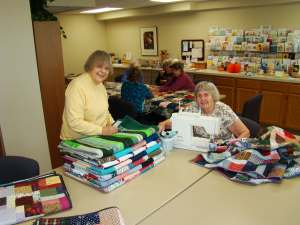 Volunteers quilting in the craft room