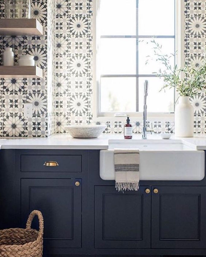 Stunning blue and white graphic tiles on sink wall of a kitchen with navy blue cabinets and farm sink. Come see 36 Best Beautiful Blue and White Kitchens to Love! #blueandwhite #bluekitchen #kitchendesign #kitchendecor #decorinspiration #beautifulkitchen